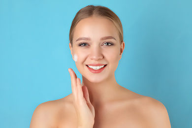 Young woman washing face with cleansing foam on light blue background. Cosmetic product