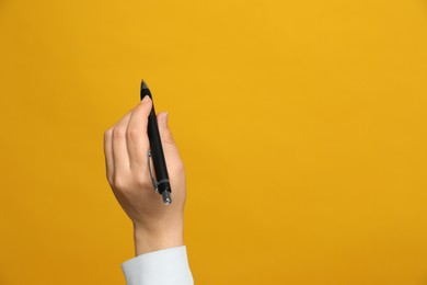 Left-handed woman holding pen on yellow background, closeup. Space for text