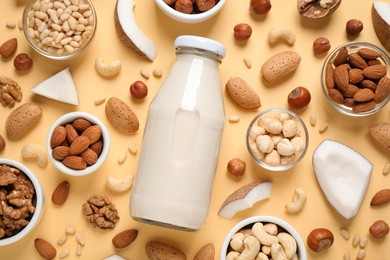 Vegan milk and different nuts on beige background, flat lay