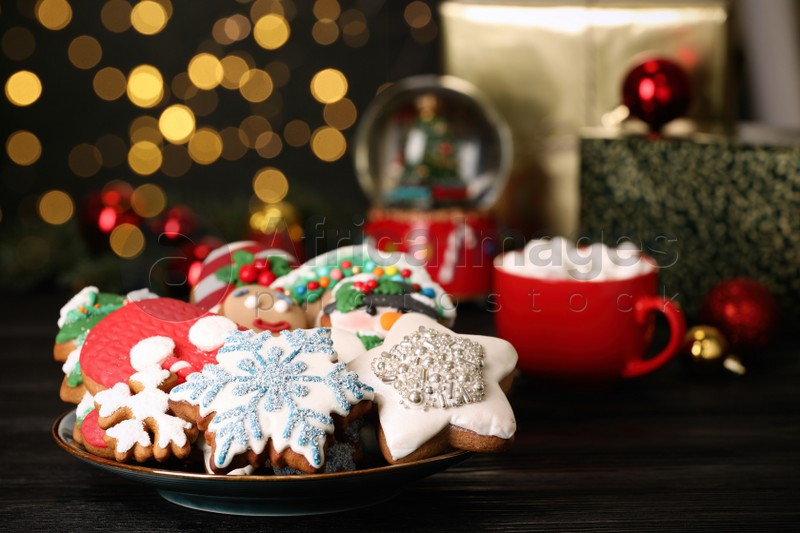 Sweet Christmas cookies and decor on black wooden table against blurred festive lights