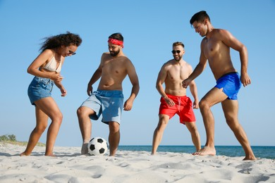 Group of friends playing football on beach