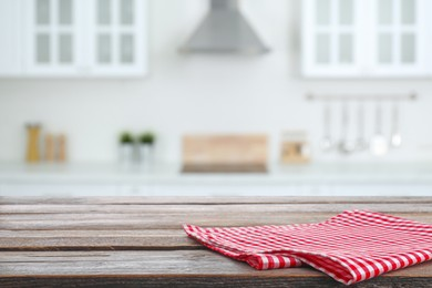 Red checkered napkin on wooden table and blurred view of stylish kitchen interior. Space for design