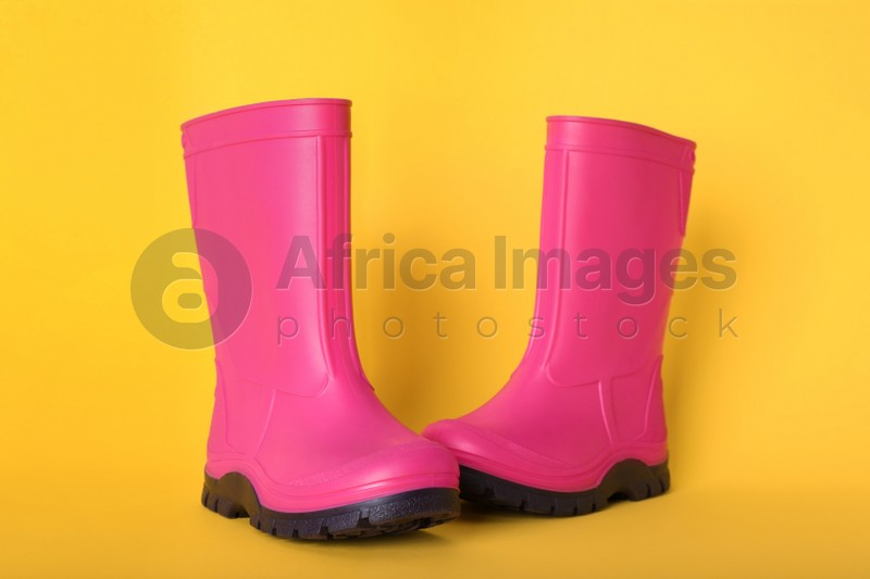 Pair of bright pink rubber boots on pale orange background