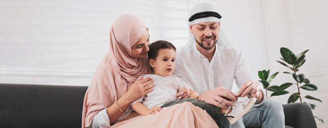 Happy Muslim family spending time together on sofa at home. Banner design