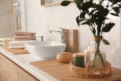 Fresh towels and beautiful branches near stylish vessel sink in bathroom. Interior design