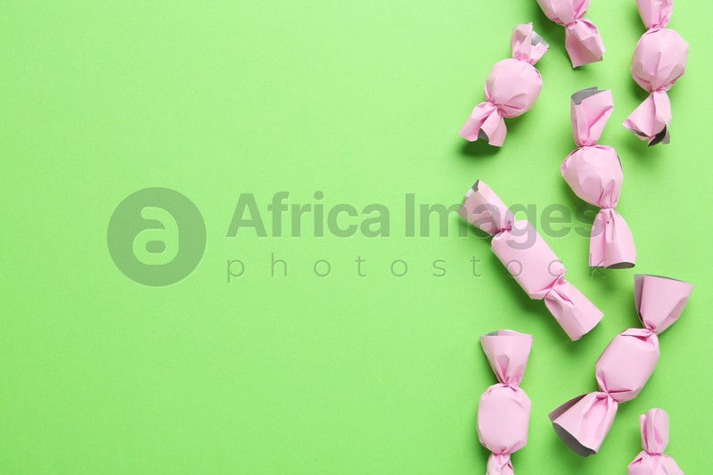 Many candies in light pink wrappers on green background, flat lay. Space for text