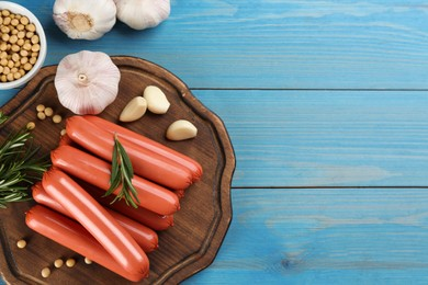 Fresh raw vegetarian sausages and vegetables on light blue wooden table, flat lay. Space for text