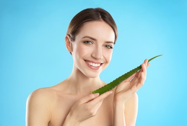 Happy young woman with aloe leaf on light blue background