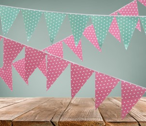 Empty wooden table and decorative bunting flags