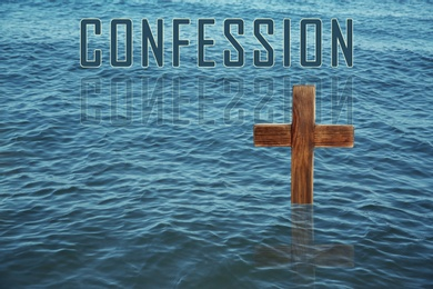 Word Confession near wooden Christian cross in water