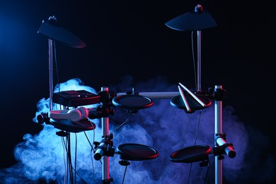 Modern electronic drum kit and smoke on dark background, color toned. Musical instrument