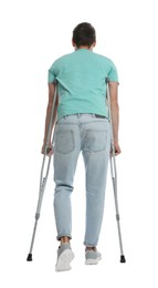 Man with crutches on white background, back view