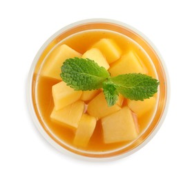 Delicious mango jelly with fresh fruit pieces and mint isolated on white, top view