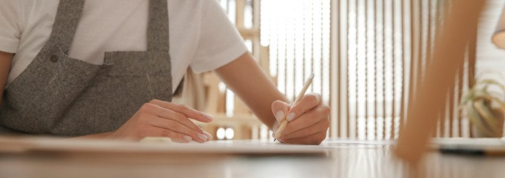 Young woman drawing with pencil at table indoors, closeup. Banner design