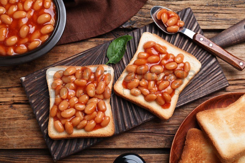 Toasts with delicious canned beans on wooden table, flat lay