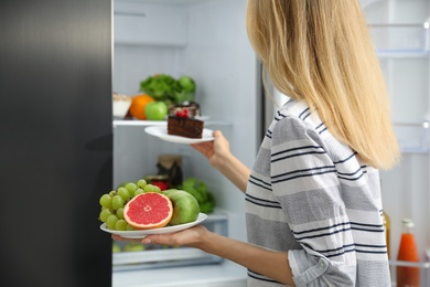 Choice concept. Woman taking plates with fruits and cake from refrigerator in kitchen, closeup