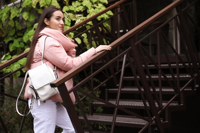 Young female traveler with stylish backpack going upstairs outdoors