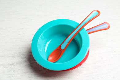 Plastic bowls with spoons on white wooden table. Serving baby food