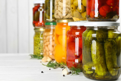 Glass jars with different pickled foods on white wooden background, closeup