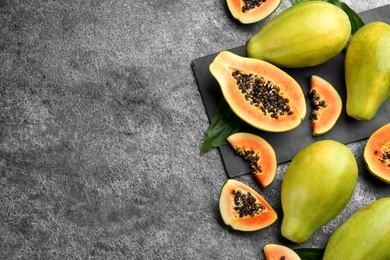 Fresh ripe papaya fruits on grey table, flat lay. Space for text