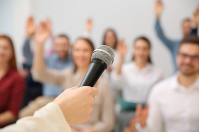 Business trainer with microphone answering questions indoors, closeup