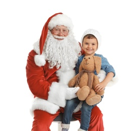 Little boy with toy bunny sitting on authentic Santa Claus' lap against white background