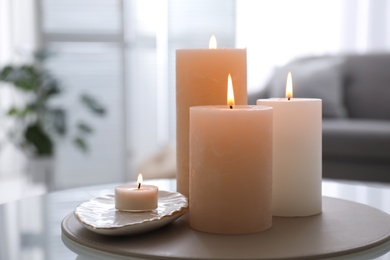 Burning candles on table indoors. Interior elements