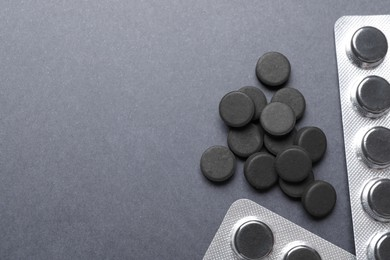 Activated charcoal pills on grey background, flat lay with space for text. Potent sorbent