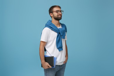 Student with books on light blue background