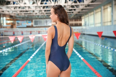 Young athletic woman standing near swimming pool