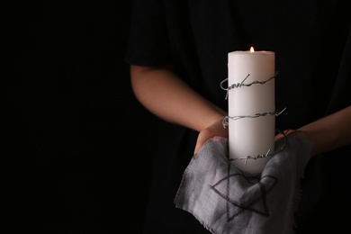 Closeup view of woman holding candle, barbed wire and fabric with David star on black background, space for text. Holocaust memory day