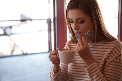 Woman with medical mask drinking coffee in cafe. Virus protection
