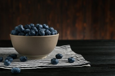 Ceramic bowl with blueberries on black wooden table, space for text. Cooking utensil