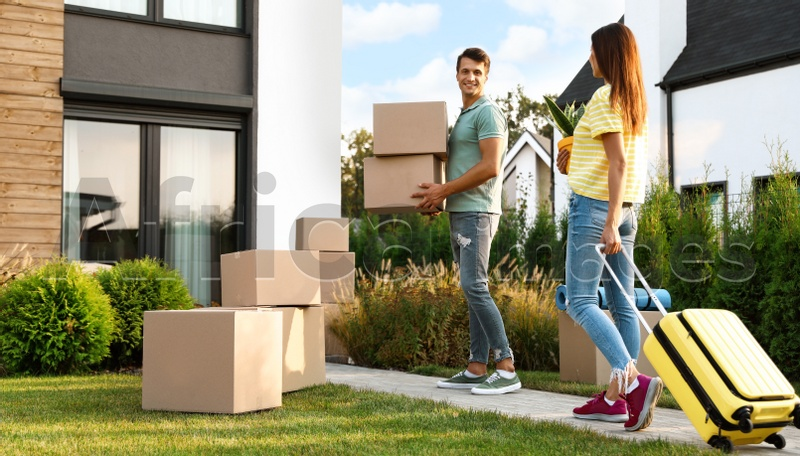 Couple walking to their new house with moving boxes and household stuff