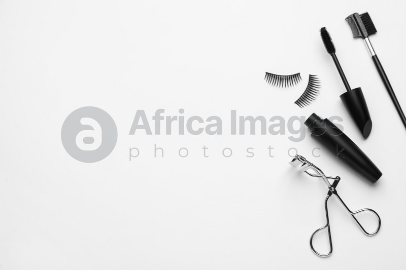 Composition with eyelash curler and mascara on white background, top view
