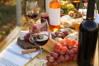 Red wine and snacks served for picnic on wooden table outdoors