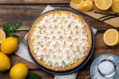 Flat lay composition with delicious lemon meringue pie on wooden table