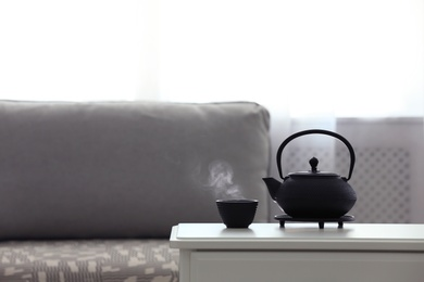 Teapot and cup of fresh hot tea on white table against blurred background. Space for text