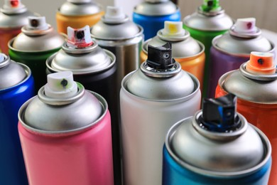 Cans of different graffiti spray paints on blurred background, closeup