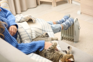 Young woman with cat warming feet on electric heater at home, closeup