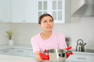 Young woman collecting leaking water from ceiling in kitchen. Time to call roof repair service