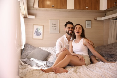 Happy young couple on bed in trailer. Camping vacation