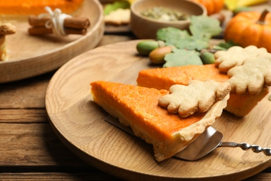 Slices of delicious homemade pumpkin pie on wooden plate, closeup