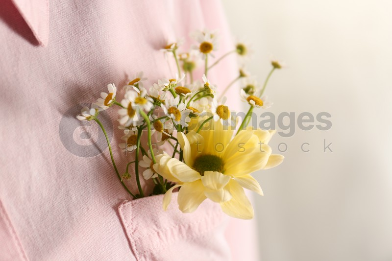 Woman with beautiful tender flowers in shirt's pocket, closeup