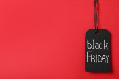 Black Friday tag on red background, space for text