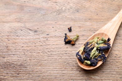Spoon and dry organic blue Anchan on wooden table, flat lay with space for text. Herbal tea