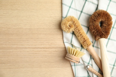 Cleaning brushes on wooden table, flat lay and space for text. Dish washing supplies