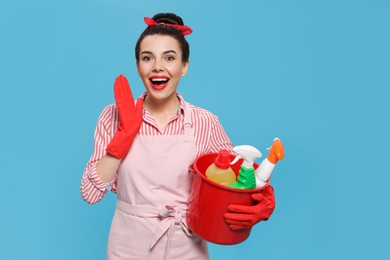 Emotional housewife holding bucket with cleaning supplies on light blue background