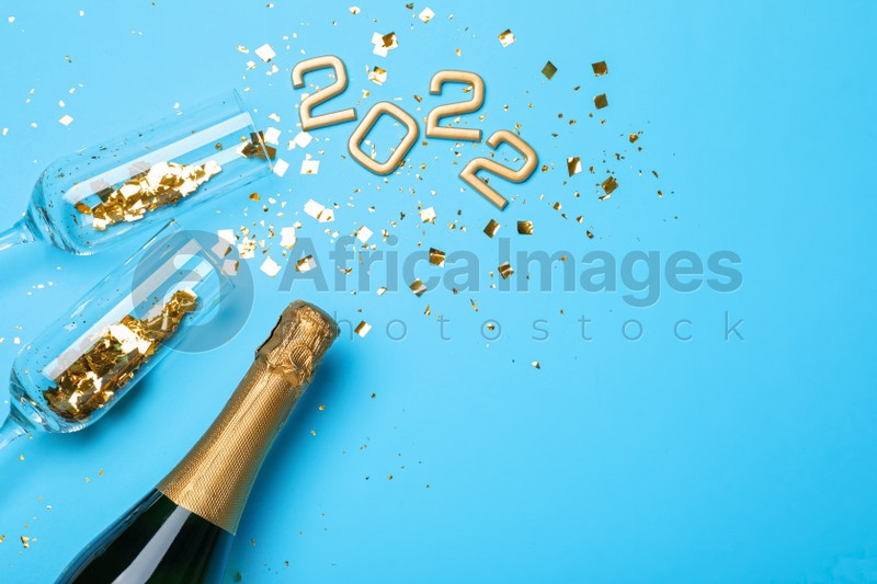 Happy New Year 2022! Flat lay composition with bottle of sparkling wine on light blue background, space for text