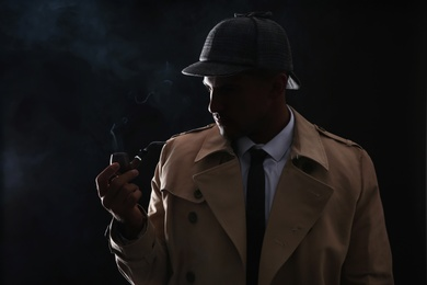 Old fashioned detective smoking pipe on dark background